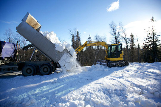 Snow saved from last season is dumped in Beitostølen, Norway. The resort opened its cross-country ski trails on schedule, but warm temperatures are jeopardizing the approaching season-opening FIS races there in November. (Photo: NSF)