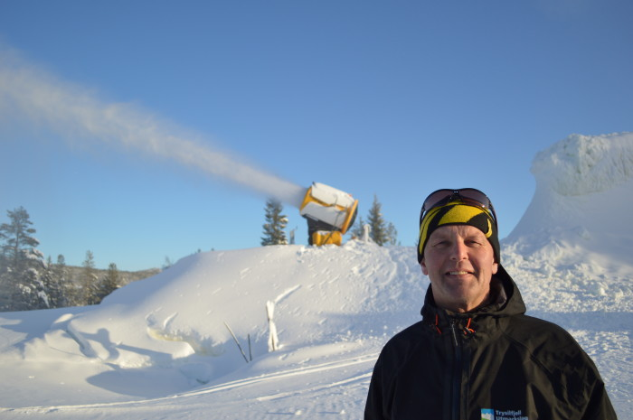 The head of Trysil's early season snow project, Ola Gerhard Sørhuus stands near a snowmaking machine and mound of snow in Trysil, Norway. (Photograph: Ole Tangnes)