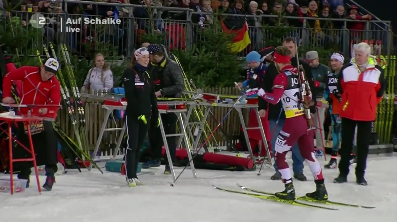 Canada Biathlon's Megan Tandy (in black) greets her relay partner Macx Davies in the tech service area after the mass start race during the 2016 Biathlon auf Schalke invitational event. (Photo: ZDF broadcast)