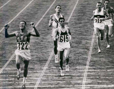 Billy Mills (Oglala Lakota), far left, crosses the finish line in first place during the 10,000 meters at the 1964 Olympic Games in Tokyo. (Photo Official Marine Corps Photo # A411758)
