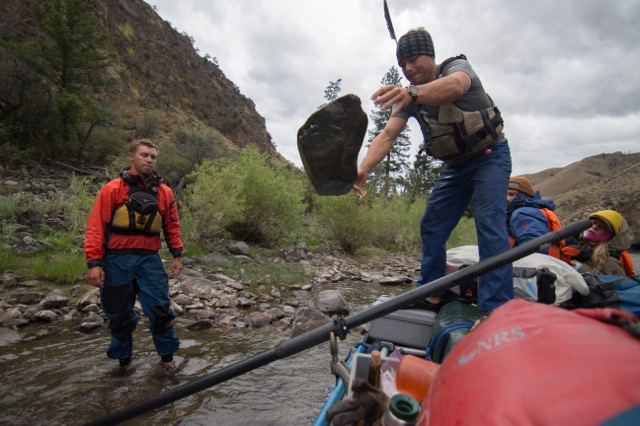 Reid Pletcher (r) hucks a rock in order to dislodge a trapped oar from the raft for the duration of a Mackay Wilderness River Journey. (Photograph: Courtesy Photo)