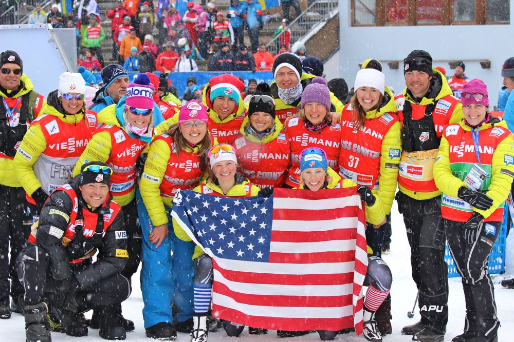 The 2013 U.S. World Championship team poses in Val di Fiemme, Italy, after Kikkan Randall and Jessie Diggins (front right, and left, with flag) won the women's freestyle team sprint.