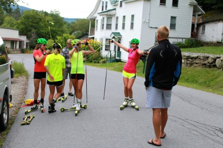Canadian Globe Cup Group coach Tor-Arne Hetland (r) talks with the SMST2 Staff throughout a water stop on its over-distance rollerski session on Aug. 15 close to Stratton, Vt.