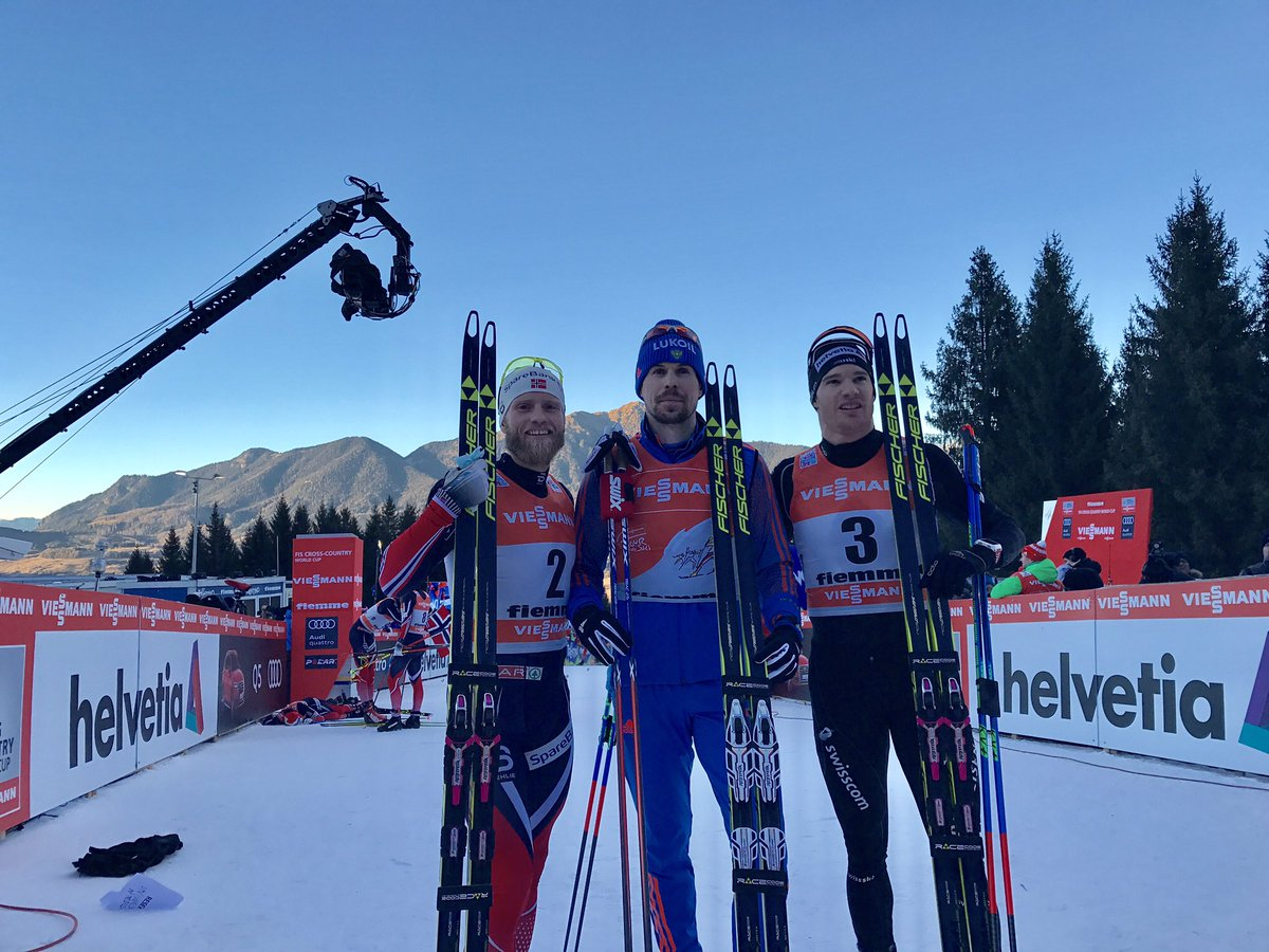 The overall podium at the end of the 2017 Tour de Ski, with winner Sergey Ustiugov (c) of Russia, Norway's Martin Johnsrud Sundby (l) in second, and Switzerland's Dario Cologna (r) in third after finishing in that order in the 9 k freestyle hill-climb pursuit, Stage 7 of the Tour de Ski in Val di Fiemme, Italy. (Photo: FIS Cross Country/Twitter)